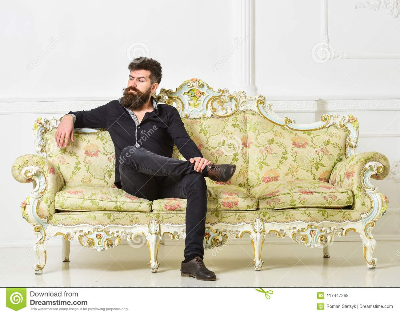 Hipster on arrogant face sits alone. Man with beard and mustache spends leisure in luxury living room. Rich and lonely