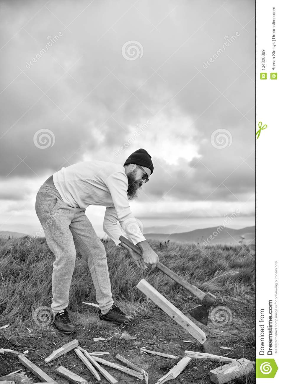 Hipster bearded man chop wood with axe on mountain landscape
