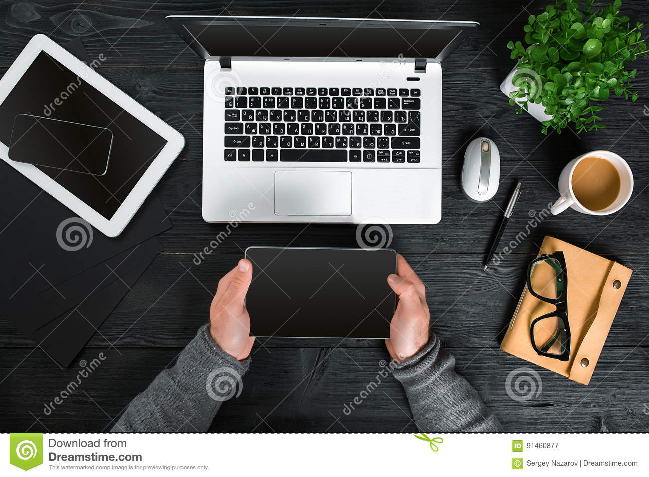 Hipster black wooden desktop top view, male hands typing on a laptop