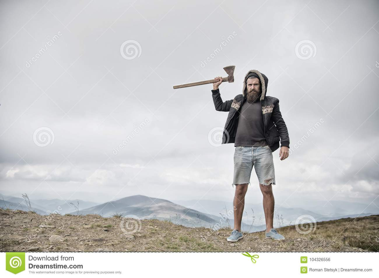 Hipster brutal bearded man with axe stand on mountain top