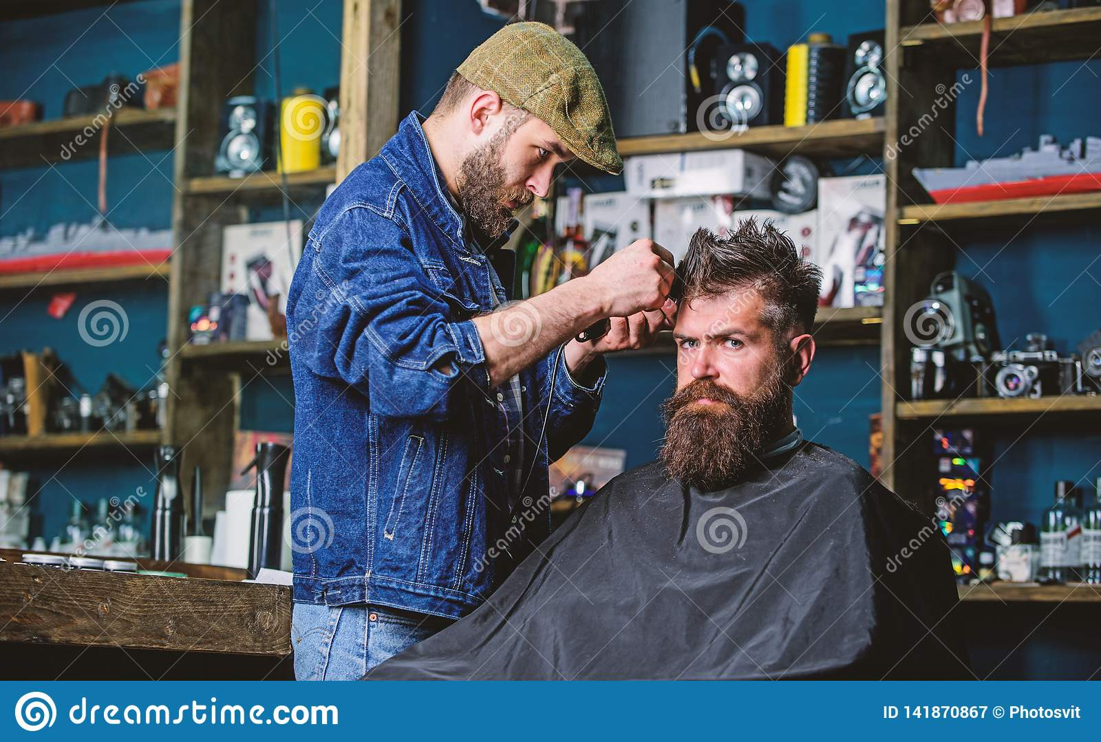 Hipster client getting haircut. Barber with hair clipper works on hairstyle for bearded man barbershop background