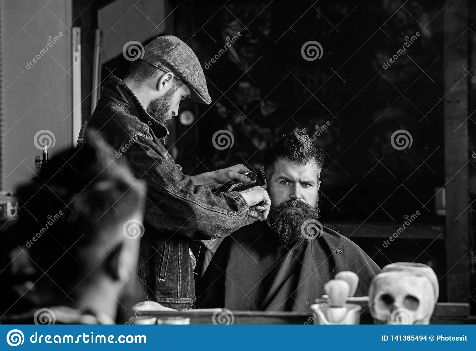 Hipster client getting haircut. Haircut concept. Barber styling hair of brutal bearded client with clipper. Barber with