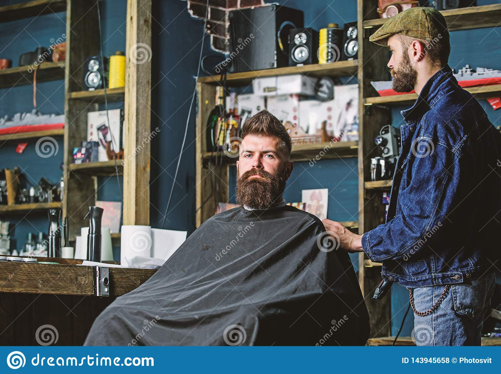 Hipster client got new haircut. Barber with hair clipper looking at mirror, barbershop background. Haircut concept