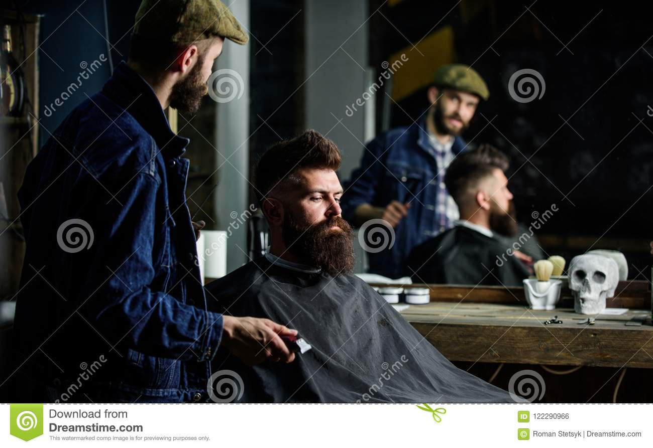Hipster client got new haircut. Barber with hair clipper looking at mirror, barbershop background. Professional master