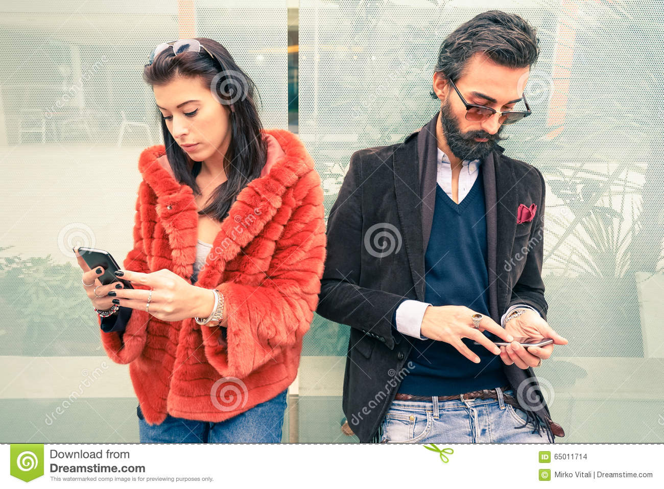 Hipster couple in sad moment ignoring each other using smartphone