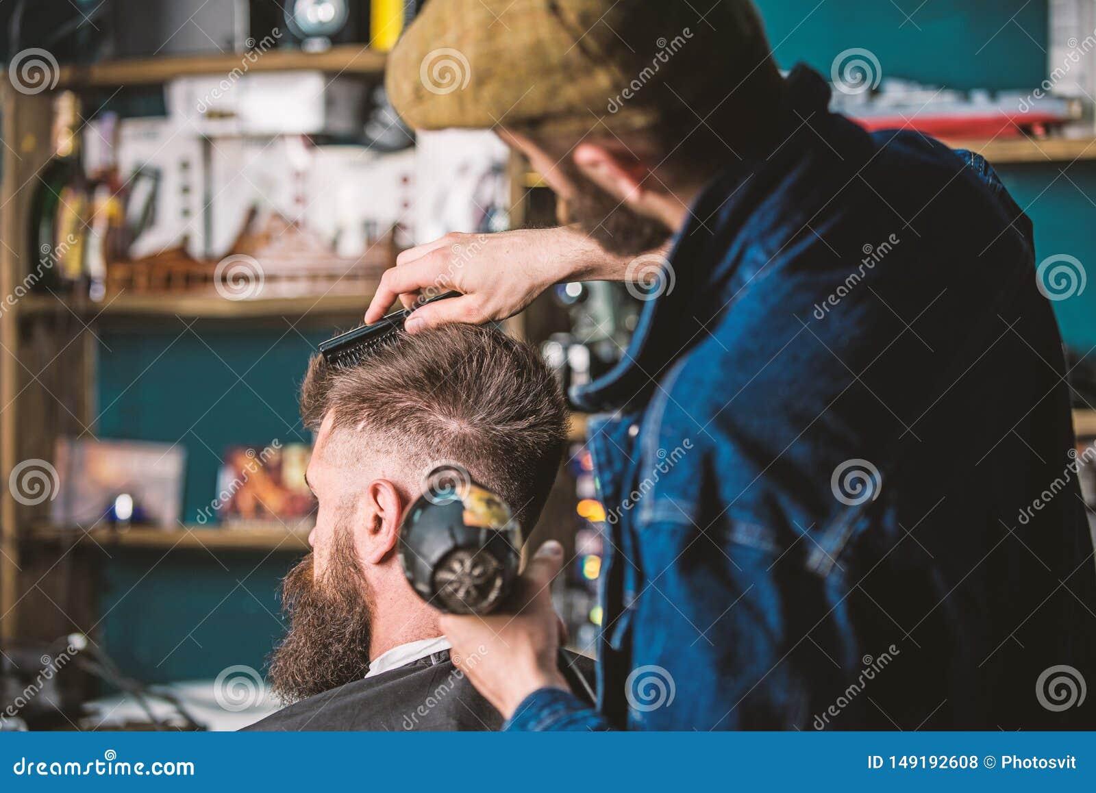 Hipster gebaarde cli?nt die kapsel krijgen Kapper met hairdryer het drogen en het stileren haar van cli?nt Kapper met hairdryer