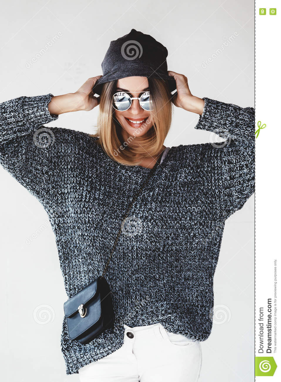 Trendy hipster girl photo in fashion urban outfit. Grey oversize sweater,  hat and sunglasses. Swag street style. Instagram photo.