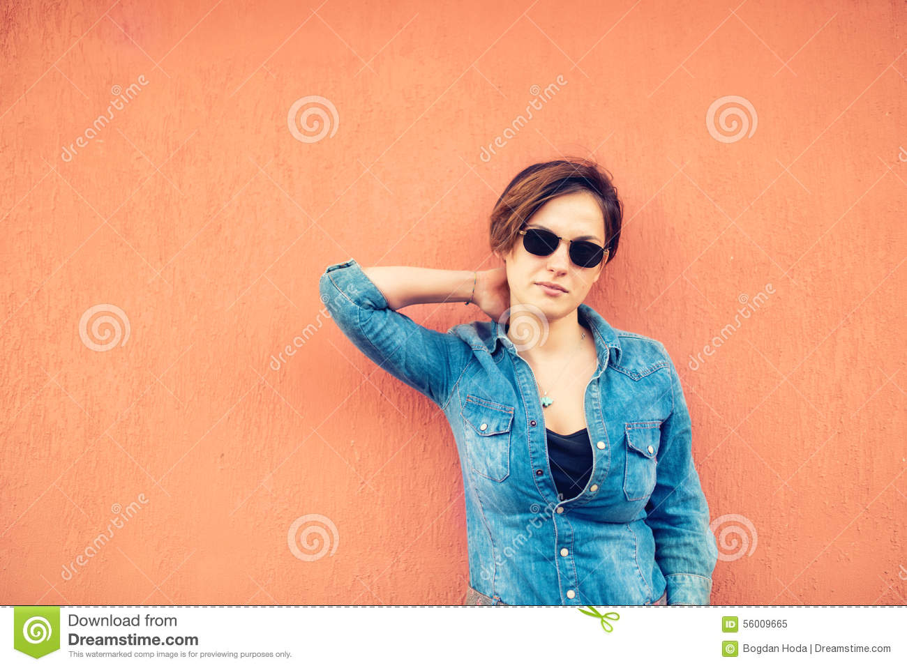 Hipster girl posing, against orange background on city streets. Urban lifestyle of contemporary world