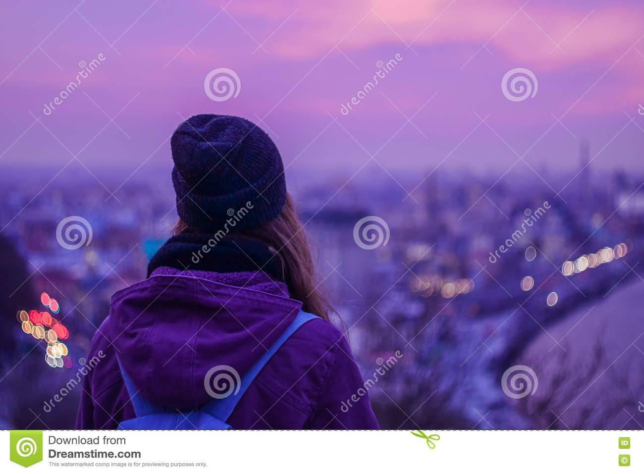 Hipster girl traveler looking at winter evening cityscape, purple violet sky and city lights