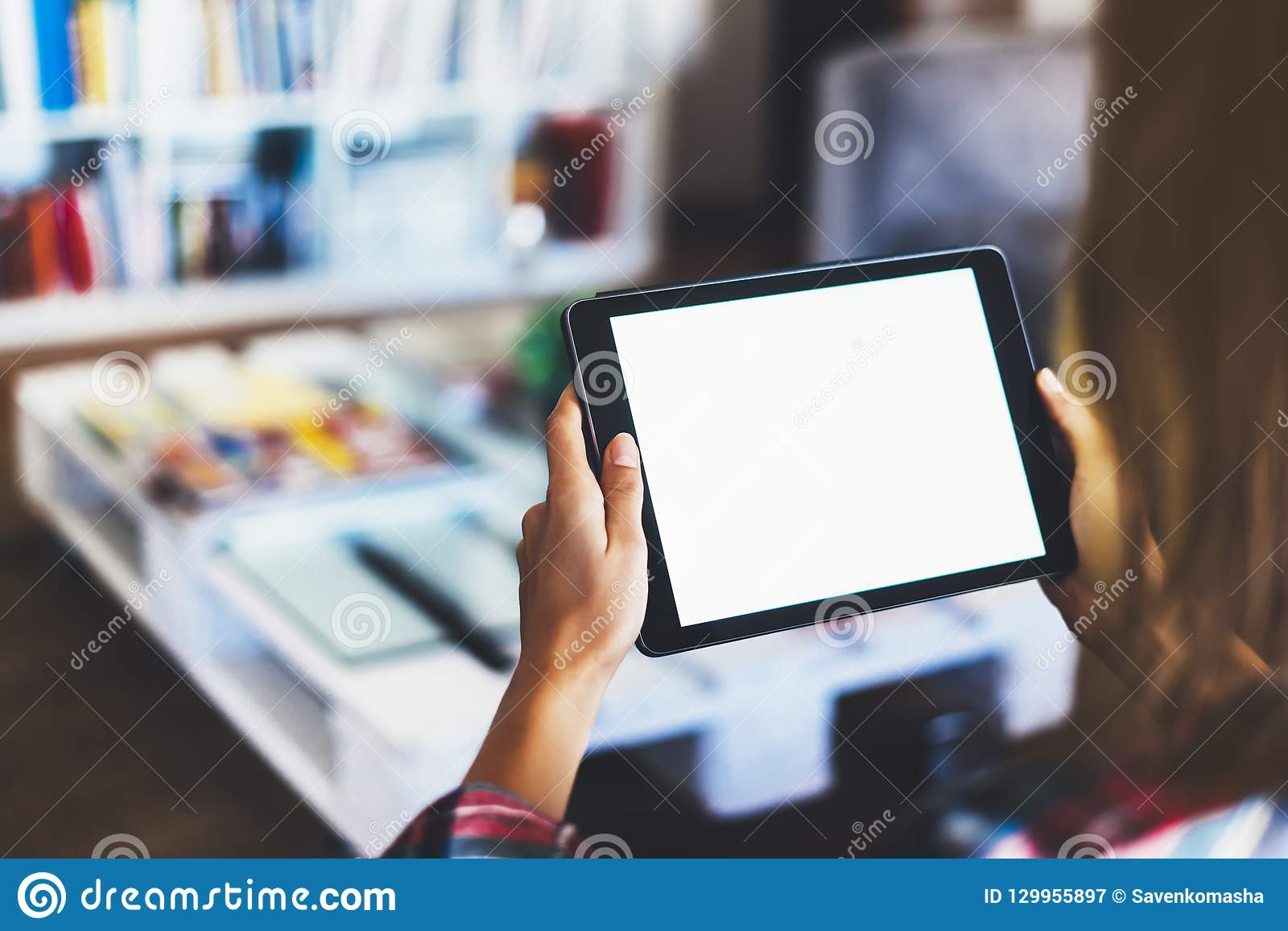 Hipster girl using tablet technology in home, blogger girl person holding computer with blank screen on background bokeh, female
