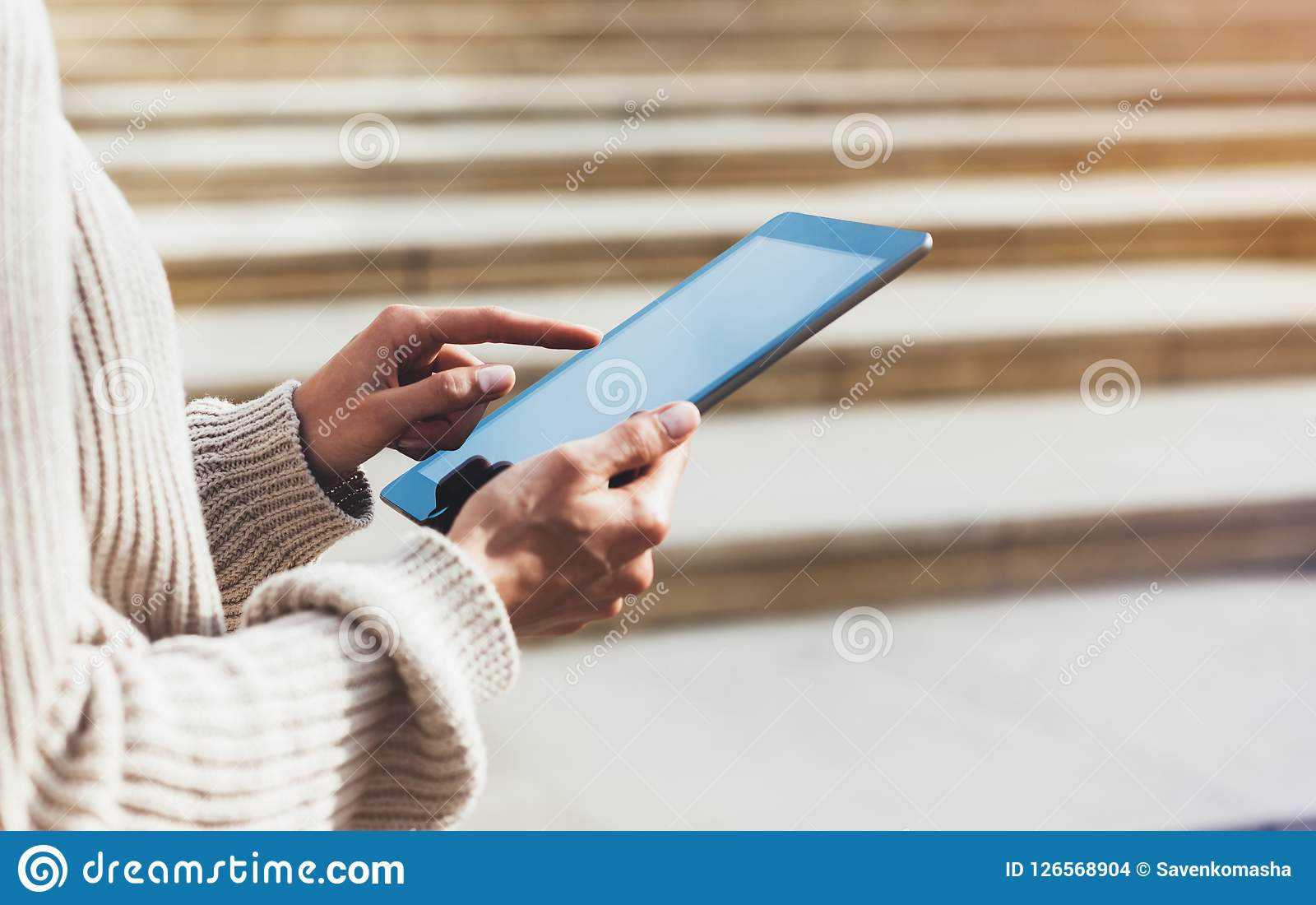 Hipster girl using tablet technology internet, blogger person holding computer on background sun city, female hands texting online