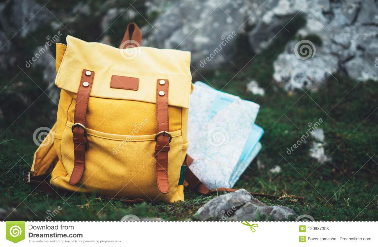 500ca0df43 Hipster hiker tourist yellow backpack and map europe on background green  grass nature in mountain