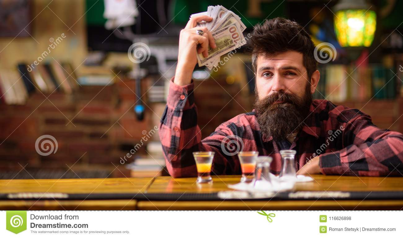 Hipster holds money, counting cash to buy more alcohol.