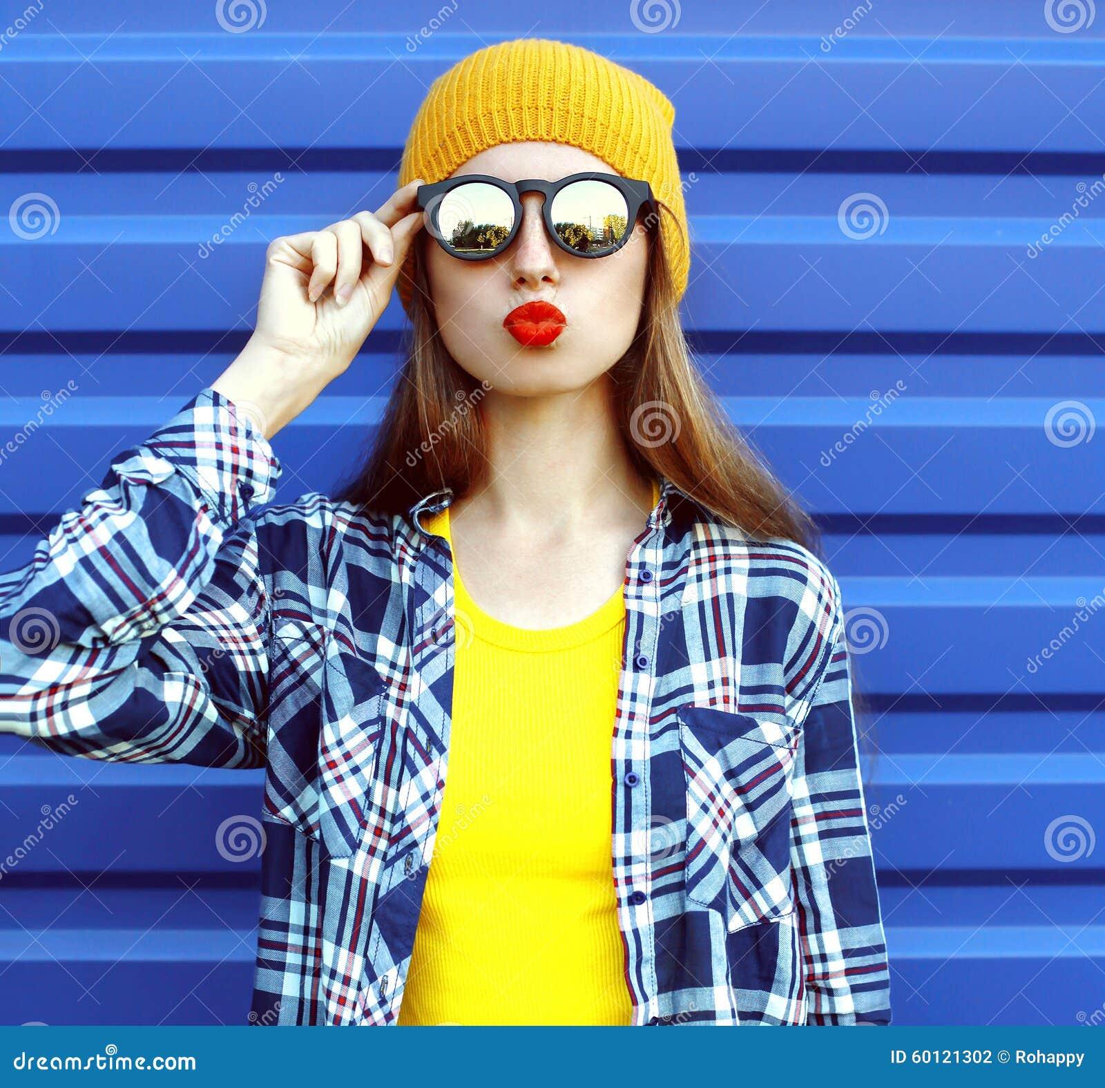 Hipster koel meisje in zonnebril en kleurrijke kleren die pret over blauw hebben