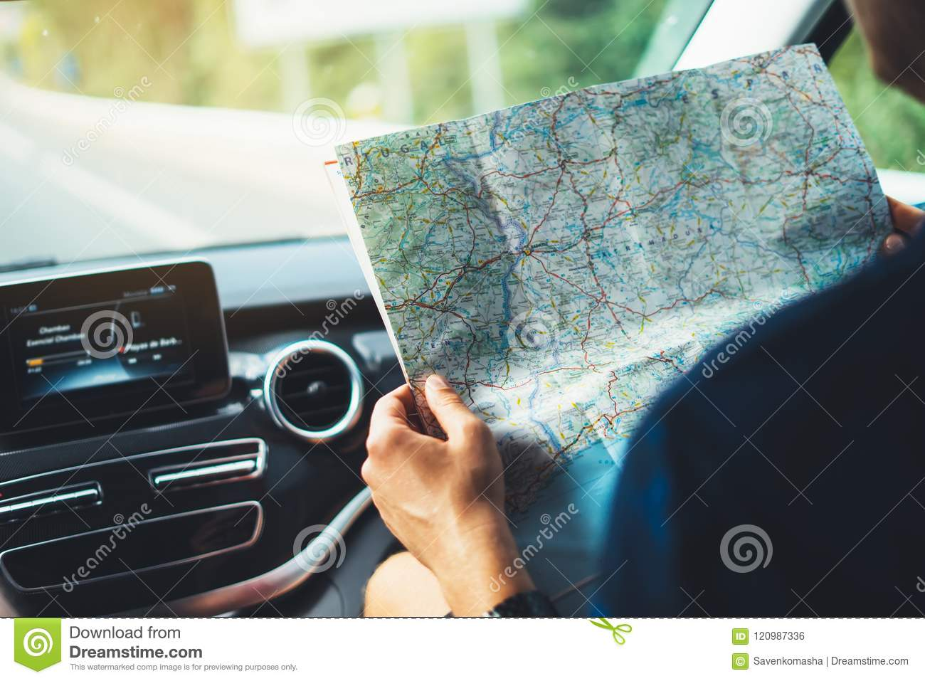 Hipster man looking and point finger on location navigation map in car, tourist traveler driving and hold in male hands europe car