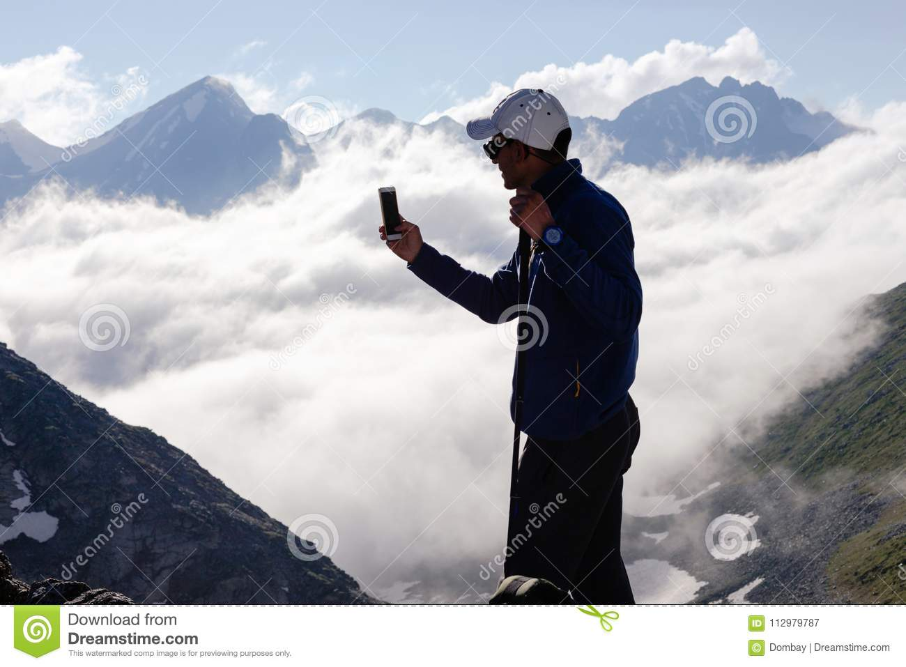 Man tourist takes pictures on mobile phone.