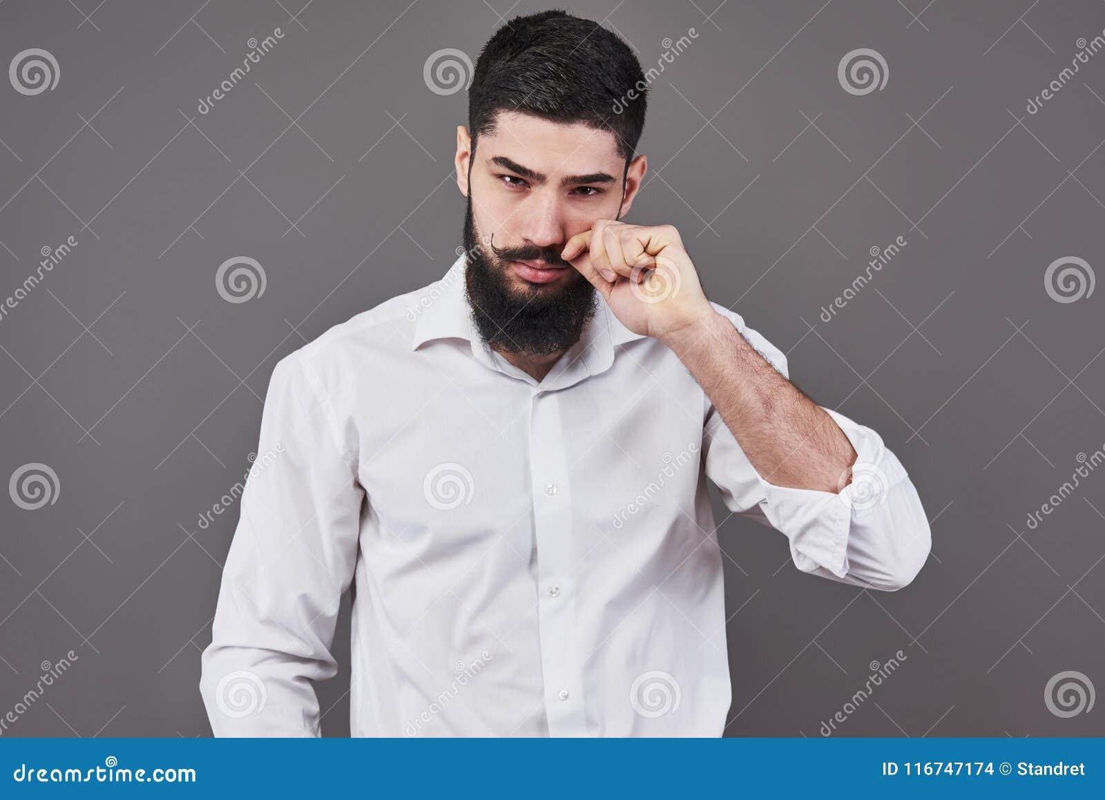 Hipster med den allvarliga framsidan mening och sinnesrörelser Grabb eller skäggig man på grå bakgrund Barberaremode och skönhet