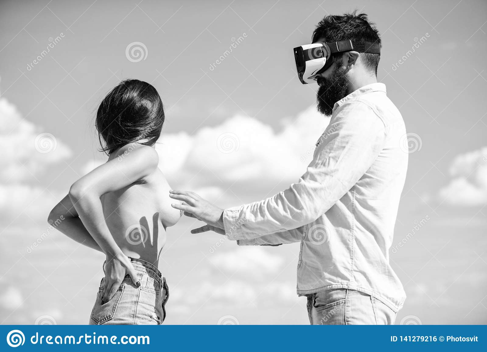Hipster man play virtual sex game hmd or vr glasses. Virtual sexual activity. Man touch naked erotic breasts