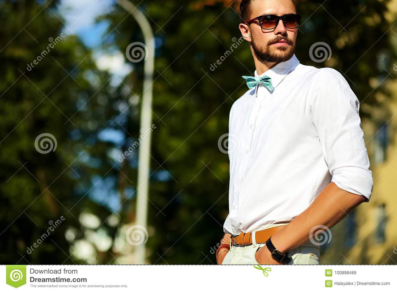 ed0a14e6fcfa Handsome hipster model man in stylish summer clothes posing on street  background in sunglasses