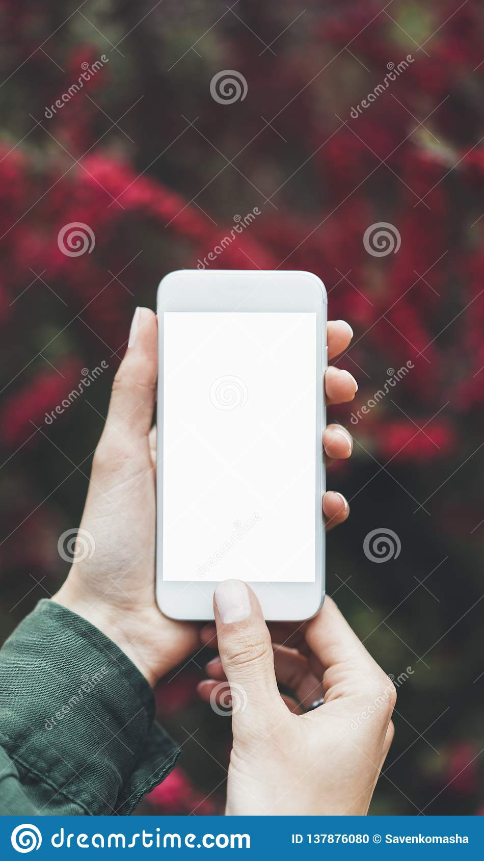 Hipster photograph on digital smartphone or technology, mock up of blank screen. Girl using cellphone on red flowers background
