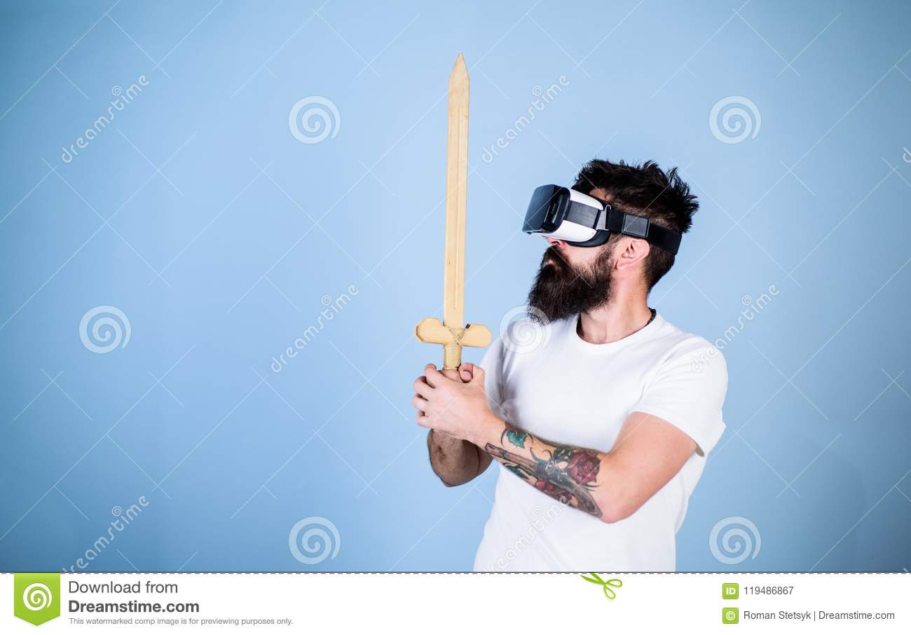 Hipster on serious face enjoy play game in virtual reality. Gamer concept. Man with beard in VR glasses, light blue