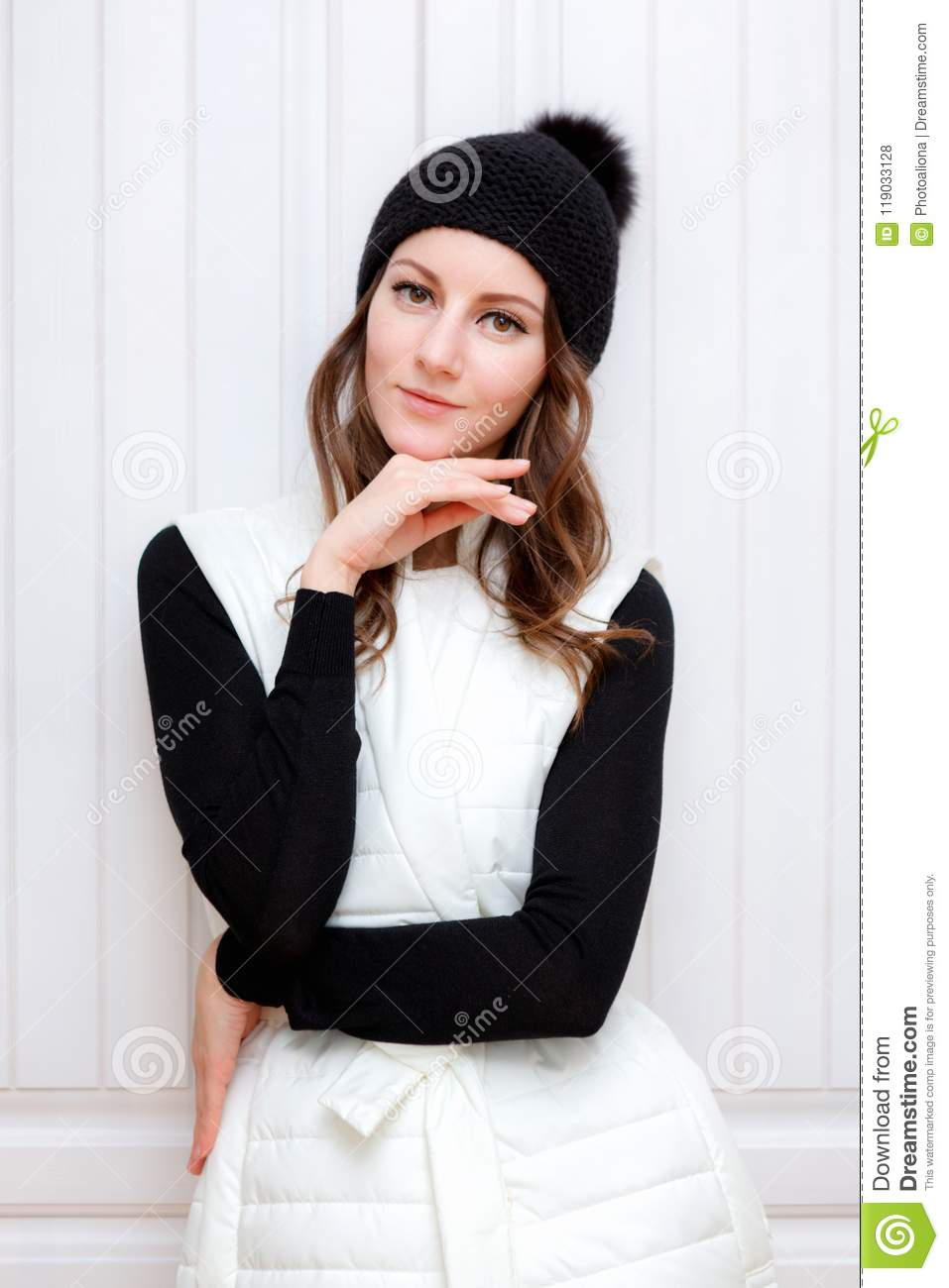 5ca8f7b0217 Hipster Style Brunette Girl Swag wearing Black fashion beanie knitted hat  with bumbon pumpon. Posing on a white wooden wardrobe background.