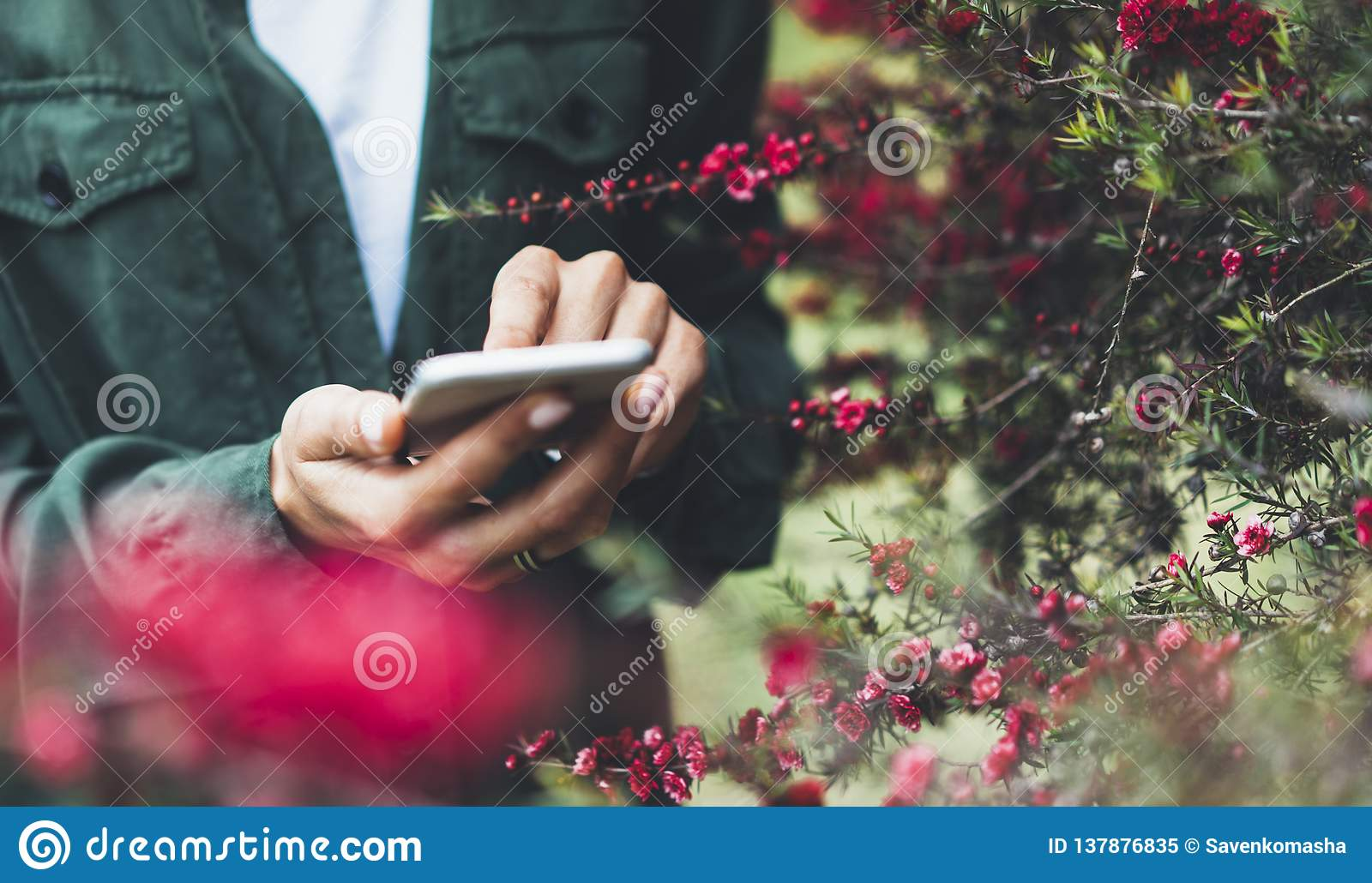 Hipster texting message on smartphone or technology, mock up of blank screen. Girl using cellphone on red flowers background close