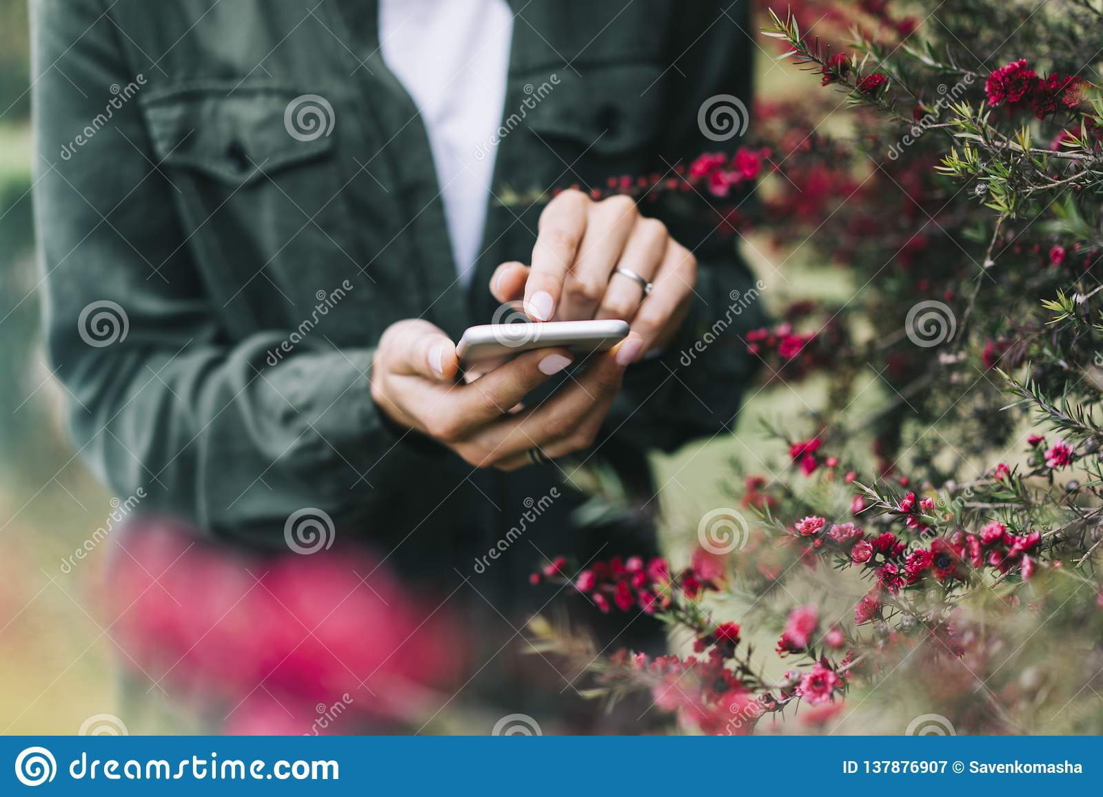 Hipster texting on smartphone or technology, mock up of blank screen. Girl using cellphone on red flowers background. Hands hold