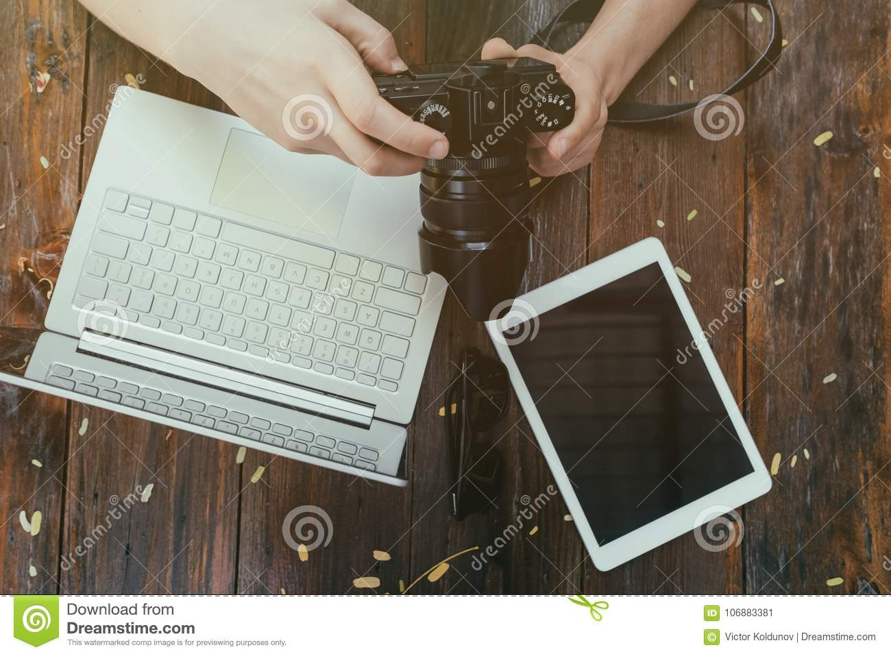 Hipster vintage wooden desktop top view, male hands holding photocamera watching photos.
