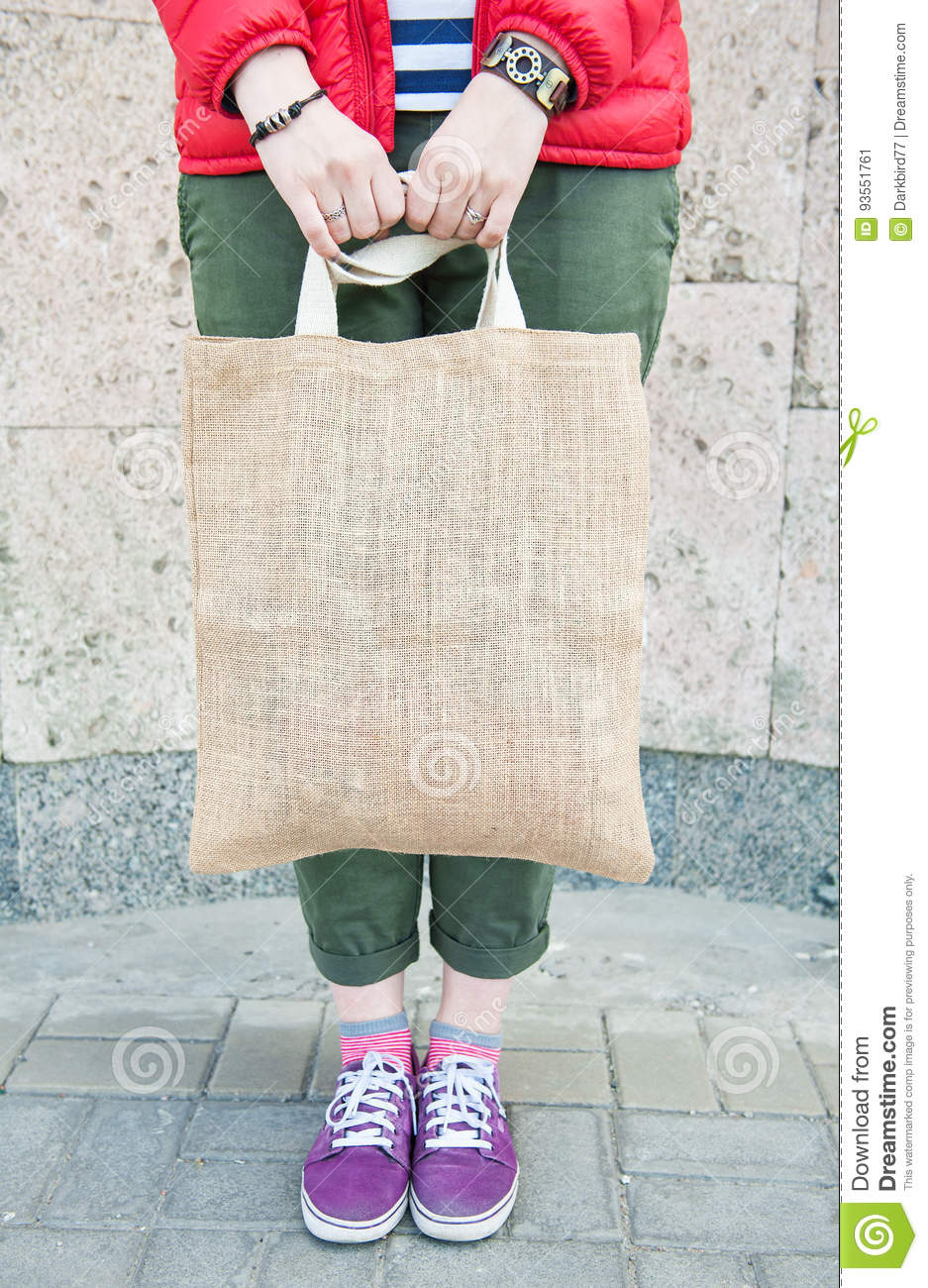 Hipster woman holding empty canvas bag outdoor. Template mock up
