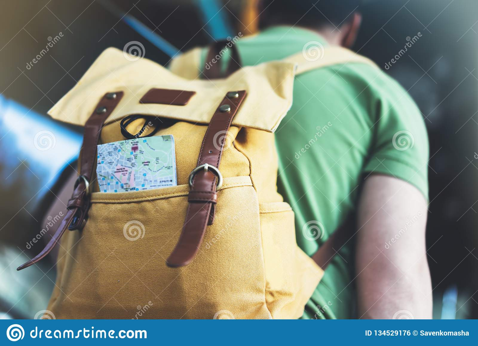 Hipster young man with backpack and map. View from back tourist traveler planning route on background sun city and pointing hand
