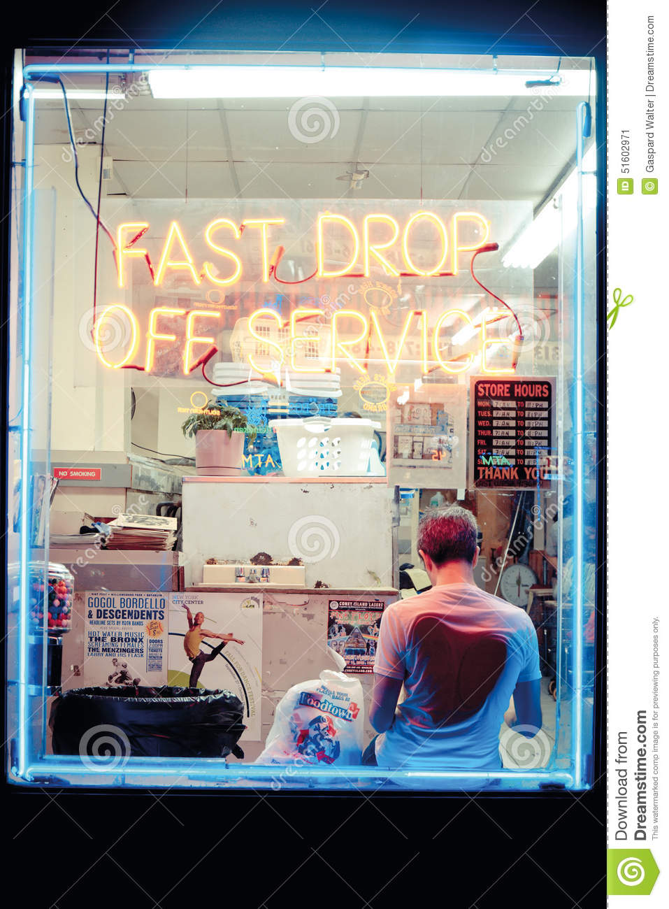 Hipster Young Man In A Laundry Shop, Reading In Front Of The Window