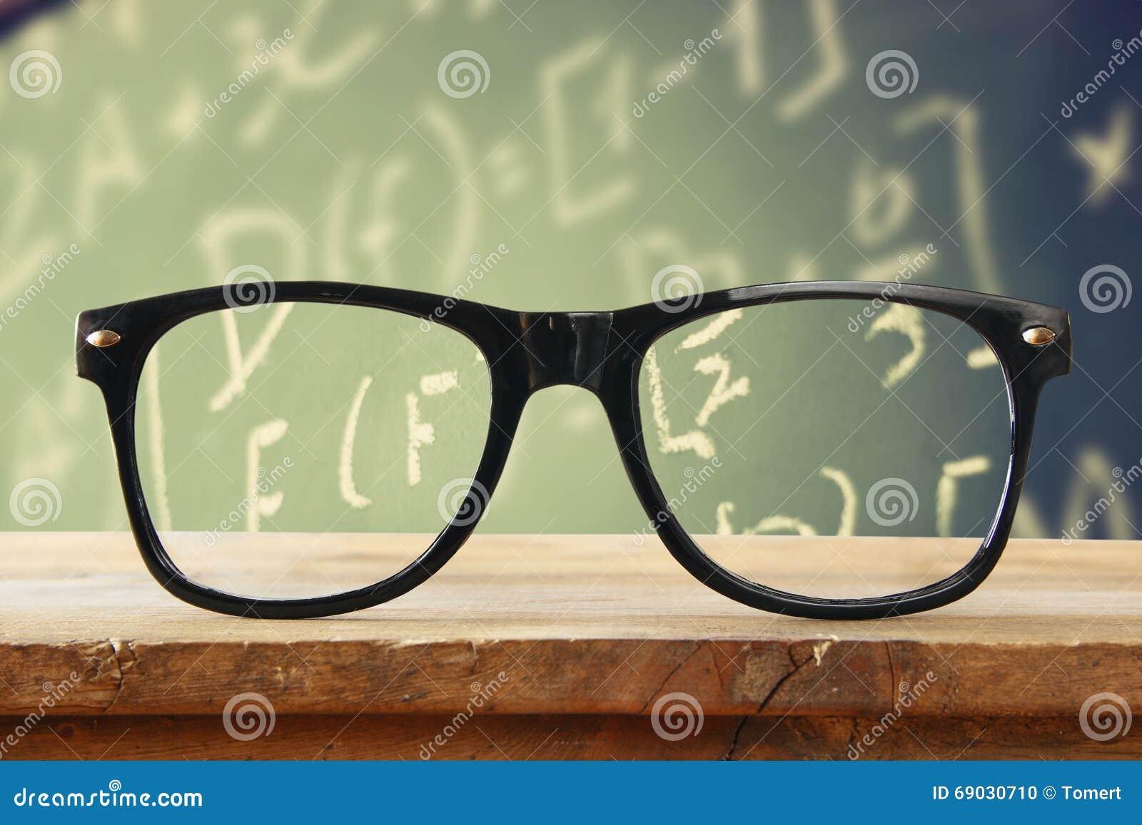 Hipsterglazen op een houten rustieke lijst vooraan bord met wiskundeformules en berekening Gefiltreerde wijnoogst