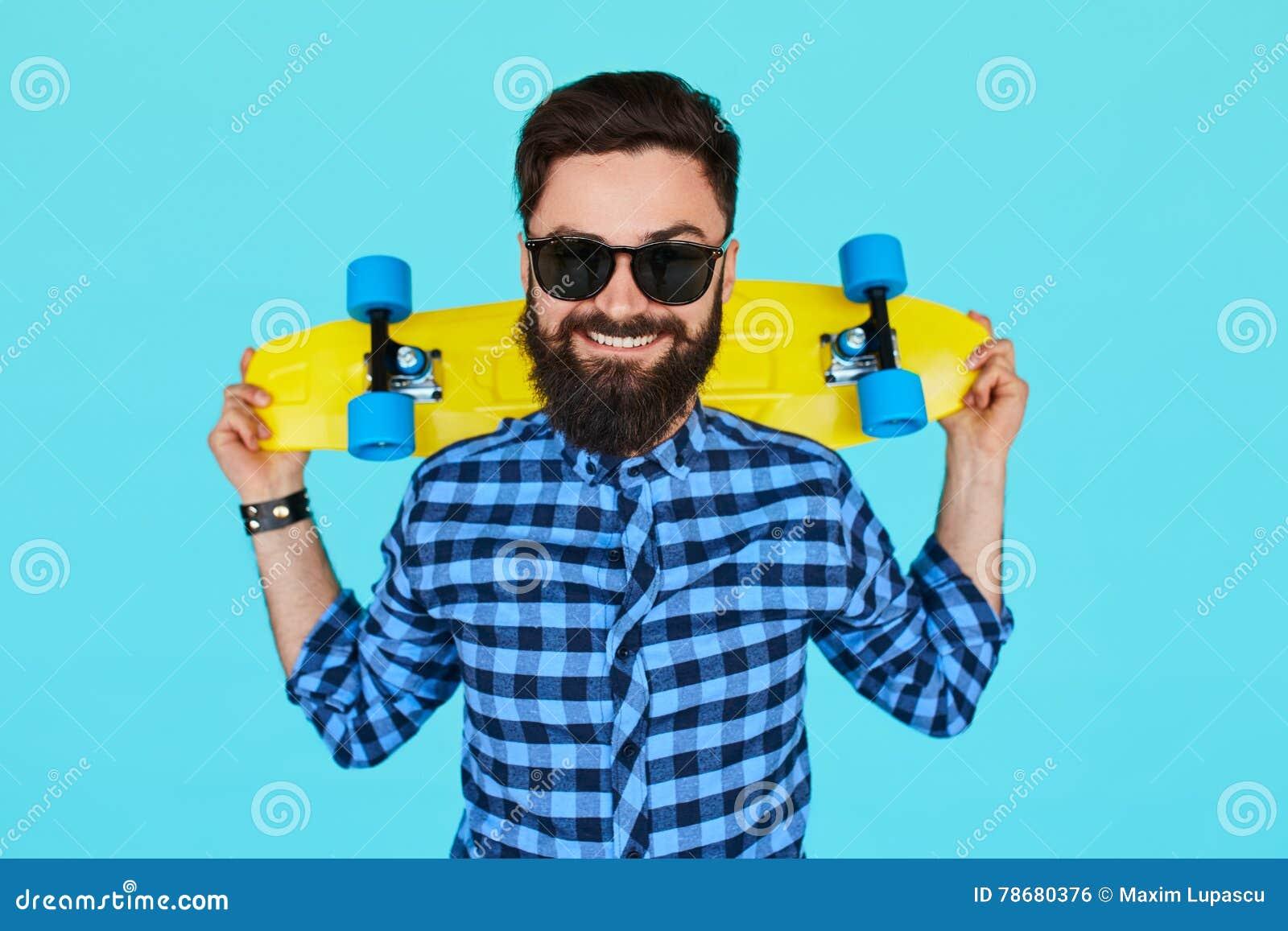 Hipsterman som rymmer en ljus vibrerande gul skateboard