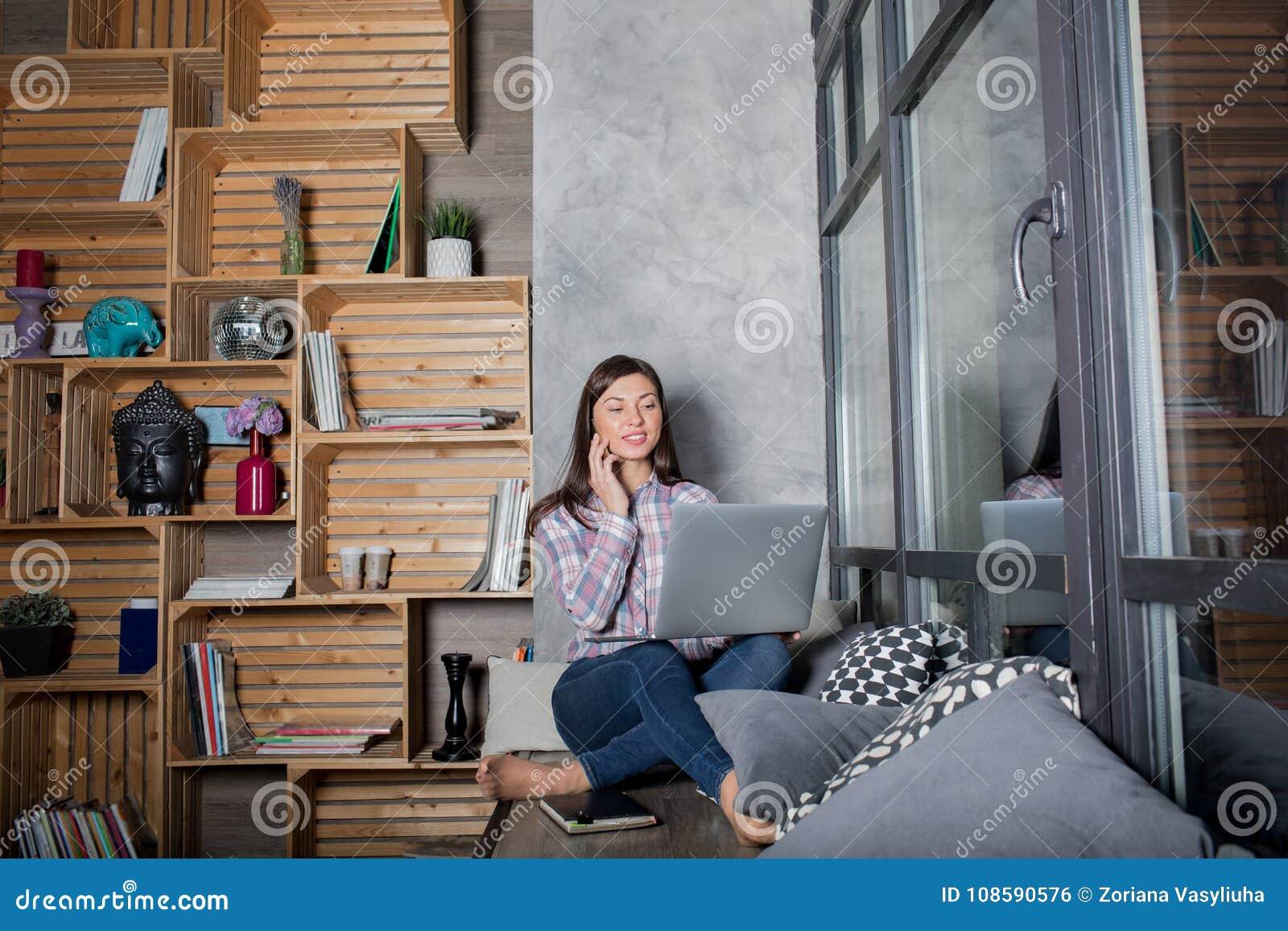 Hipstermeisje die op celtelefoon spreken en aan netto-boek tijdens recreatietijd werken