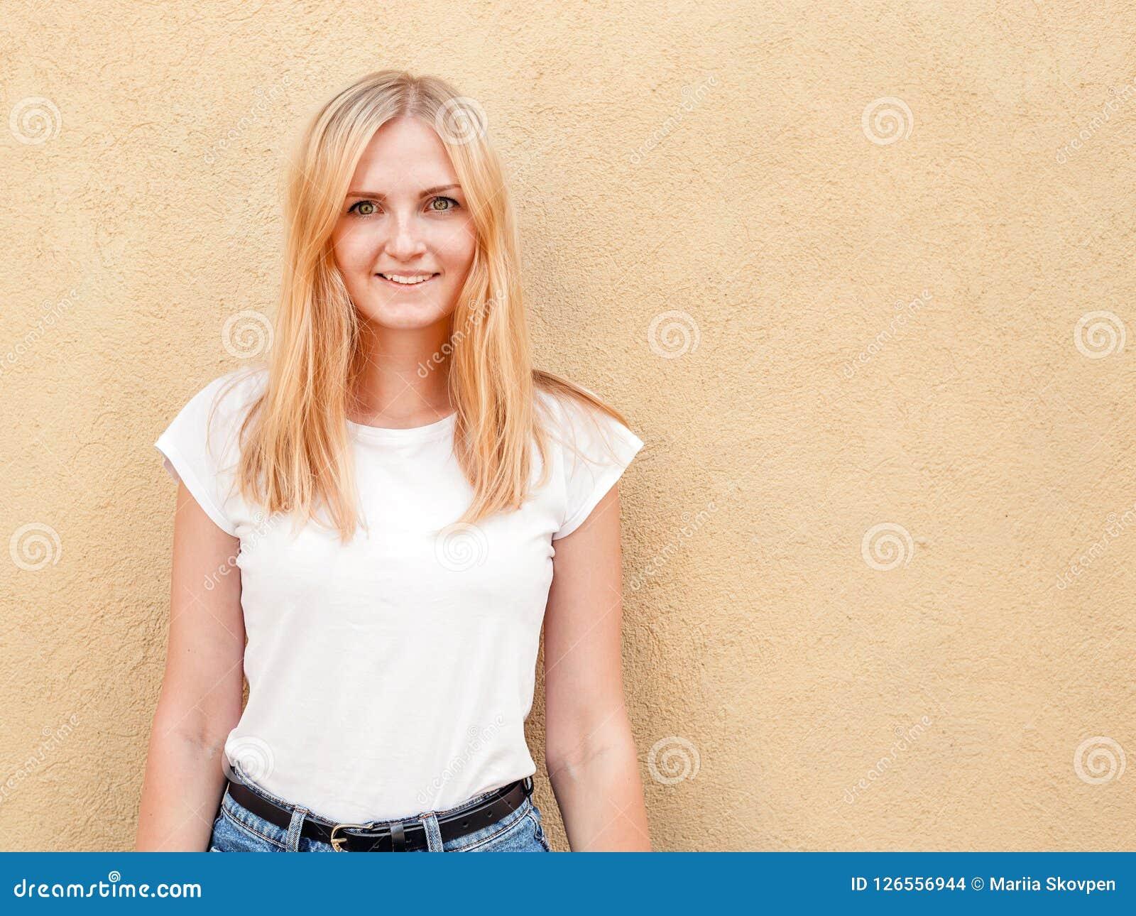 Hipstermeisje lege witte t-shirt dragen en jeans die tegen ruwe straatmuur stellen, minimalistische stedelijke kledingsstijl