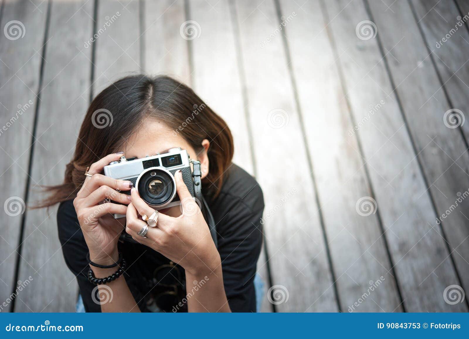Hipstervrouw die foto s met retro filmcamera nemen op het houten park van de floorofstad, mooi die meisje in de oude camera wordt