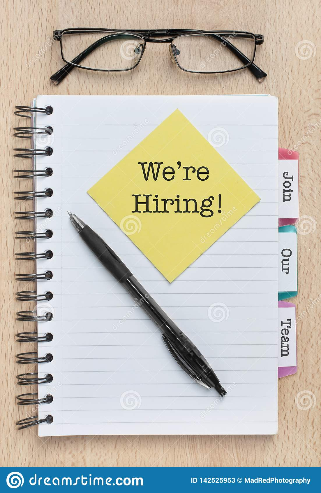 We Are Hiring, Join Our Team. Text written on a sticky note on a notebook, next to a pen and glasses