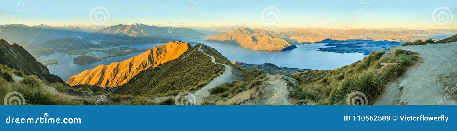 Hisnande och att bedöva panorama- landskapsikt från det Roys maximumet på sjön Wanaka med guld- solskenljus på skymning, södra ö