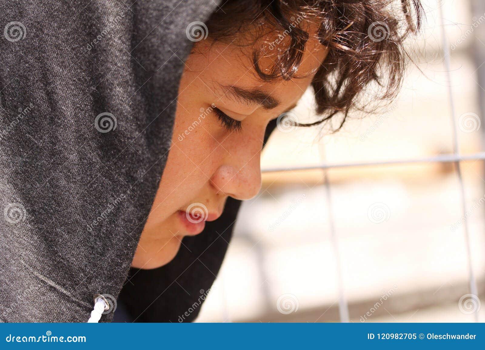 Hispânico incomodado triste 13 de velha escola anos de adolescente do menino que veste um levantamento do hoodie exterior - ascen
