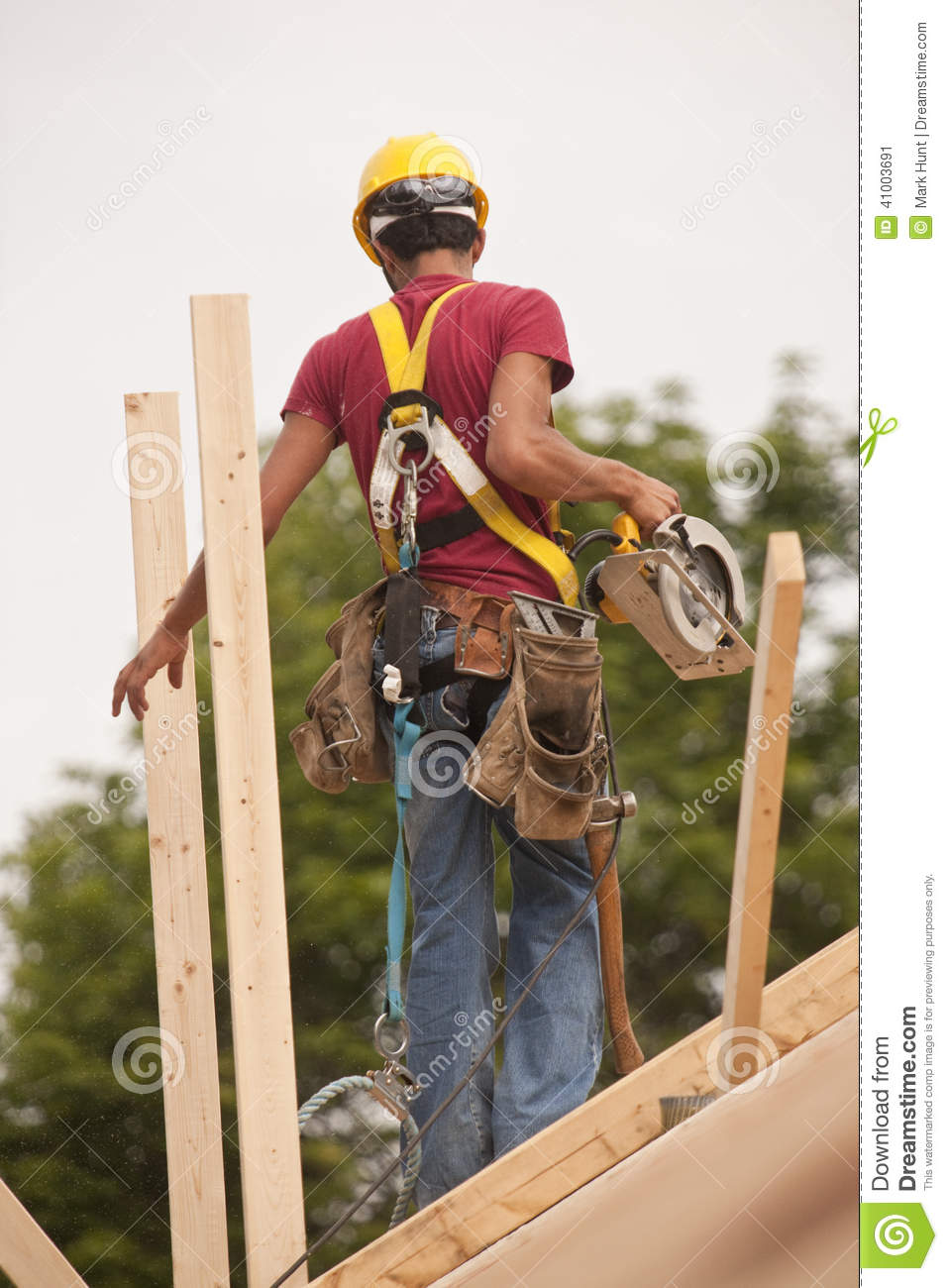 Hispanic Carpenter Holding Circular Saw On Roof Stock