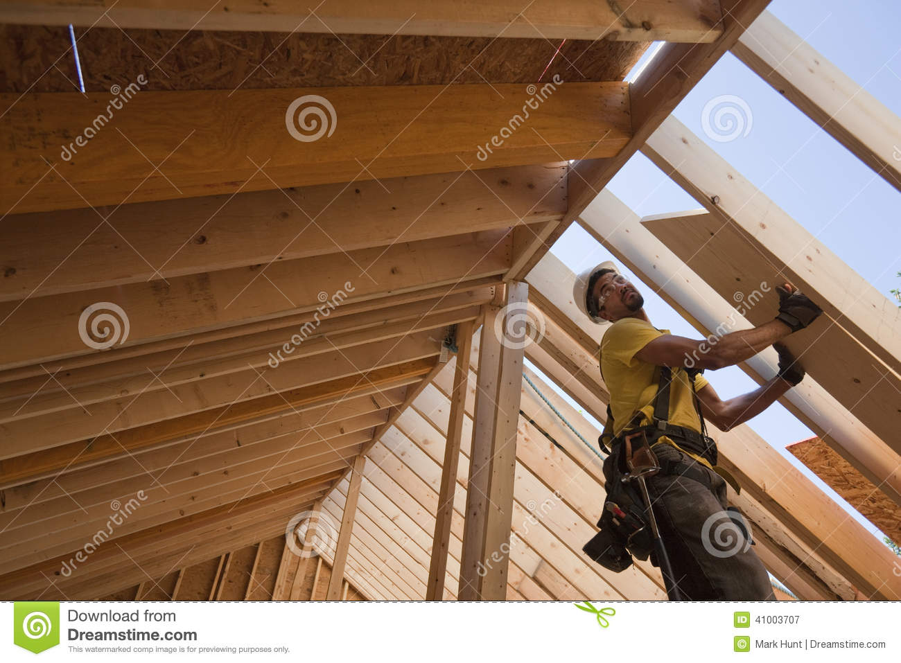 Hispanic Carpenter Lifting Roofing Panels Onto Roof Stock