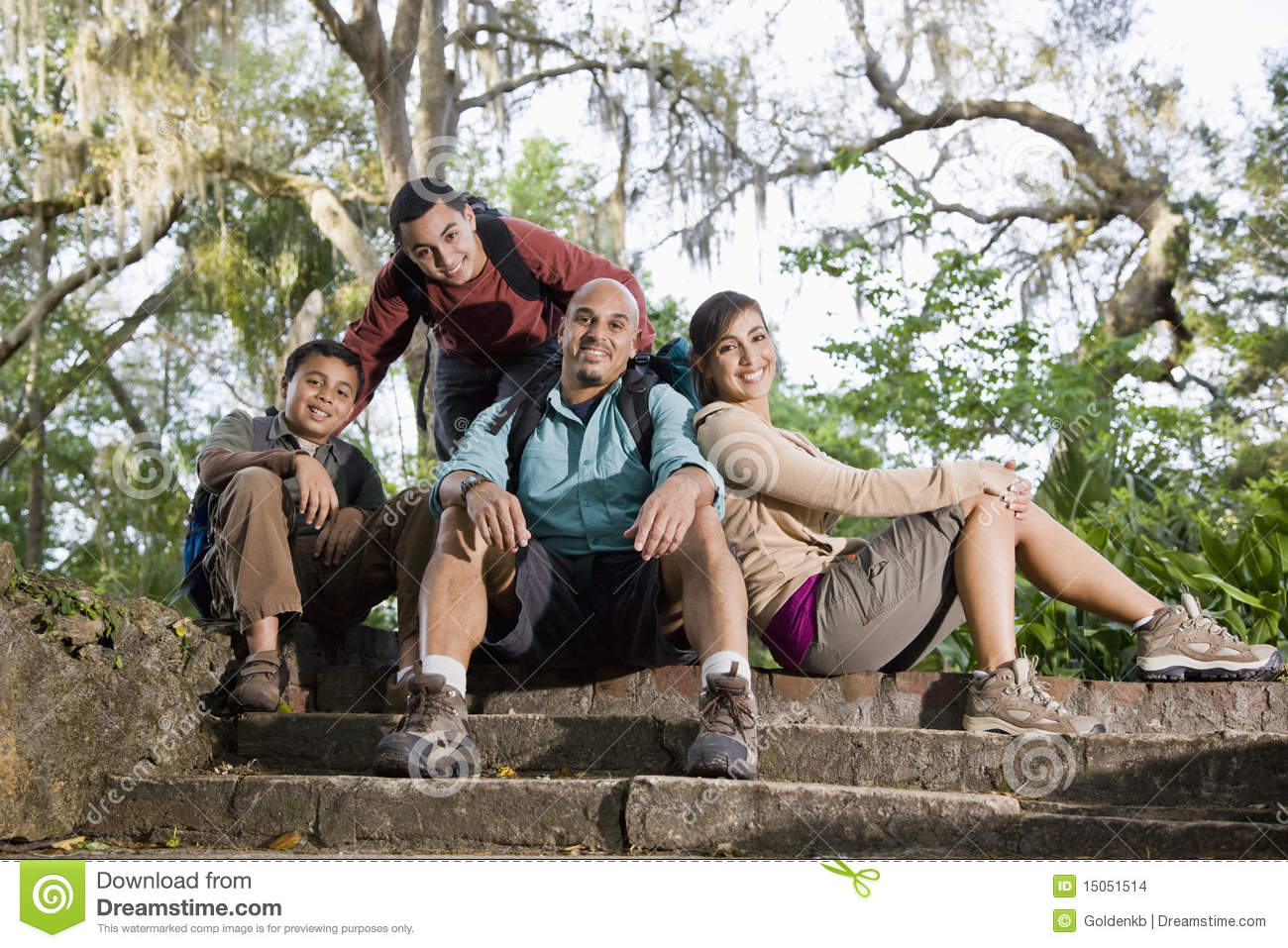 Hispanic Family With Backpacks Hiking In Park Smiling Full
