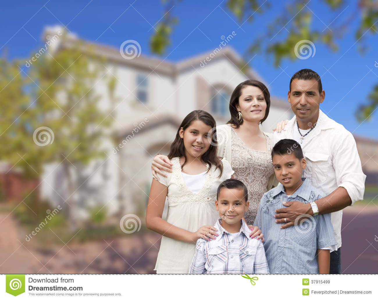 hispanic family in front of beautiful house royalty free