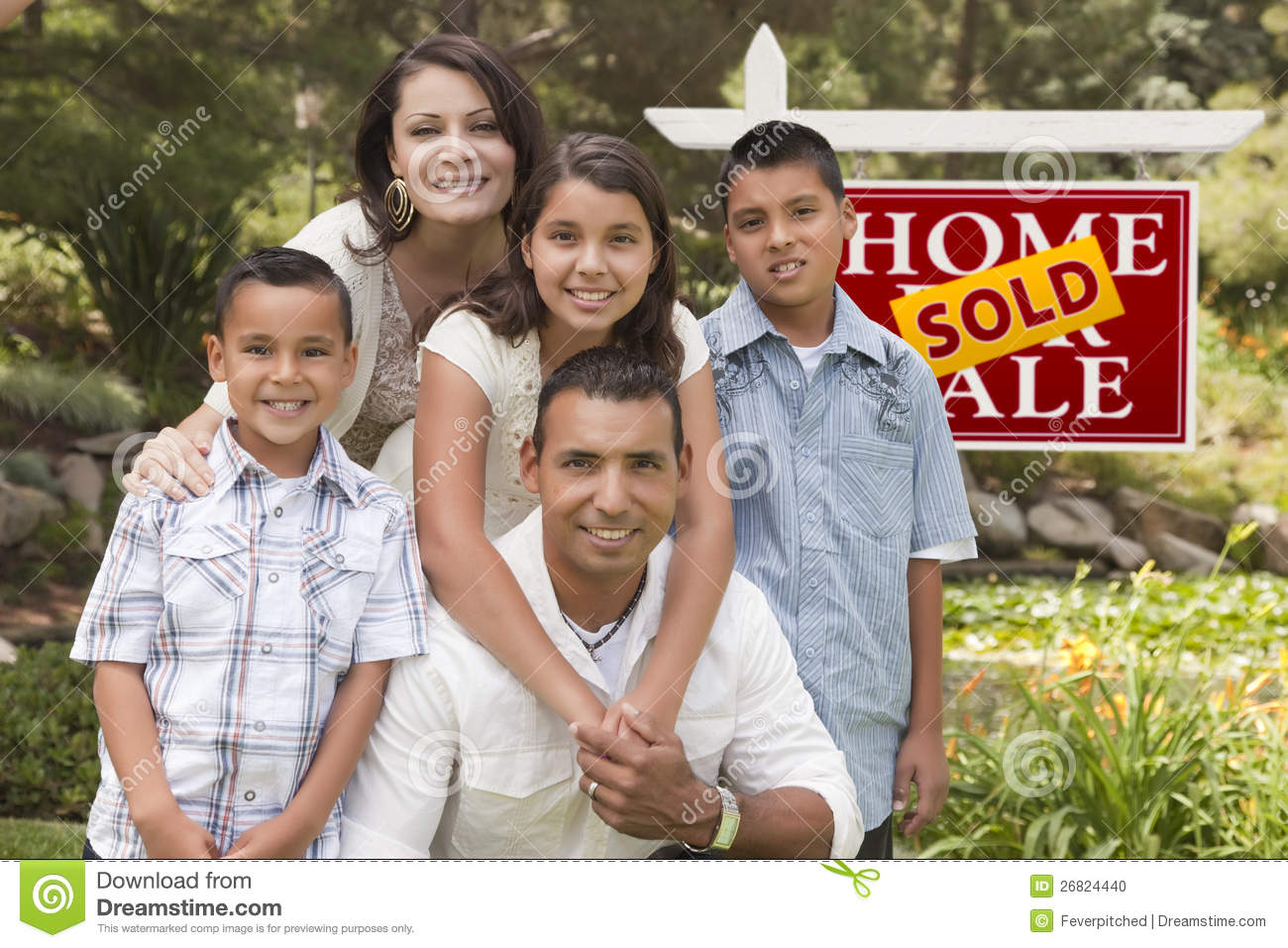 Hispanic Family in Front of Sold Real Estate Sign