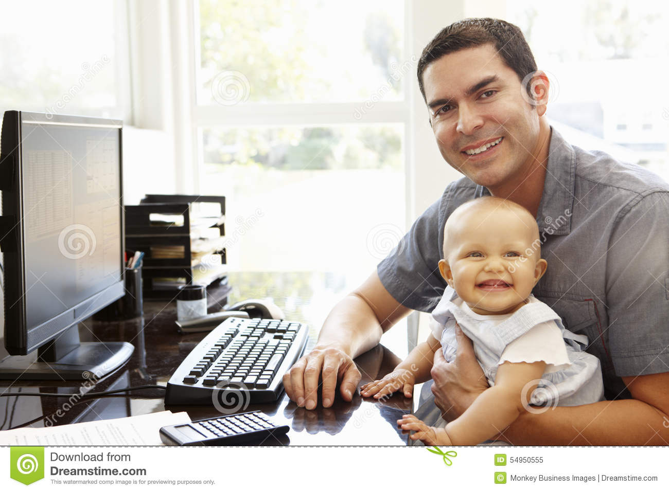 Working In Home Office hispanic father with baby working in home office stock photo