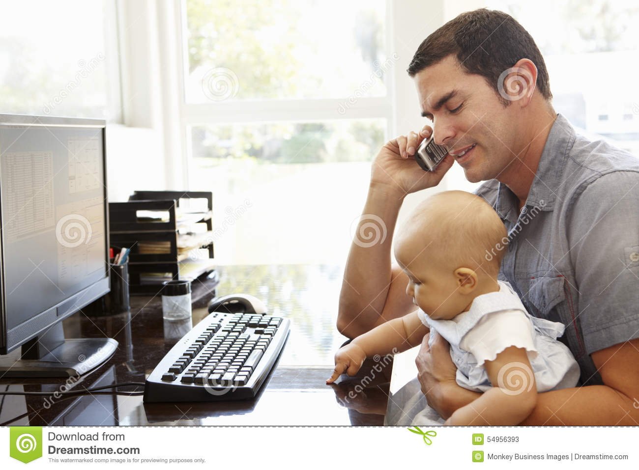 Hispanic Father With Baby Working In Home Office Stock Photo