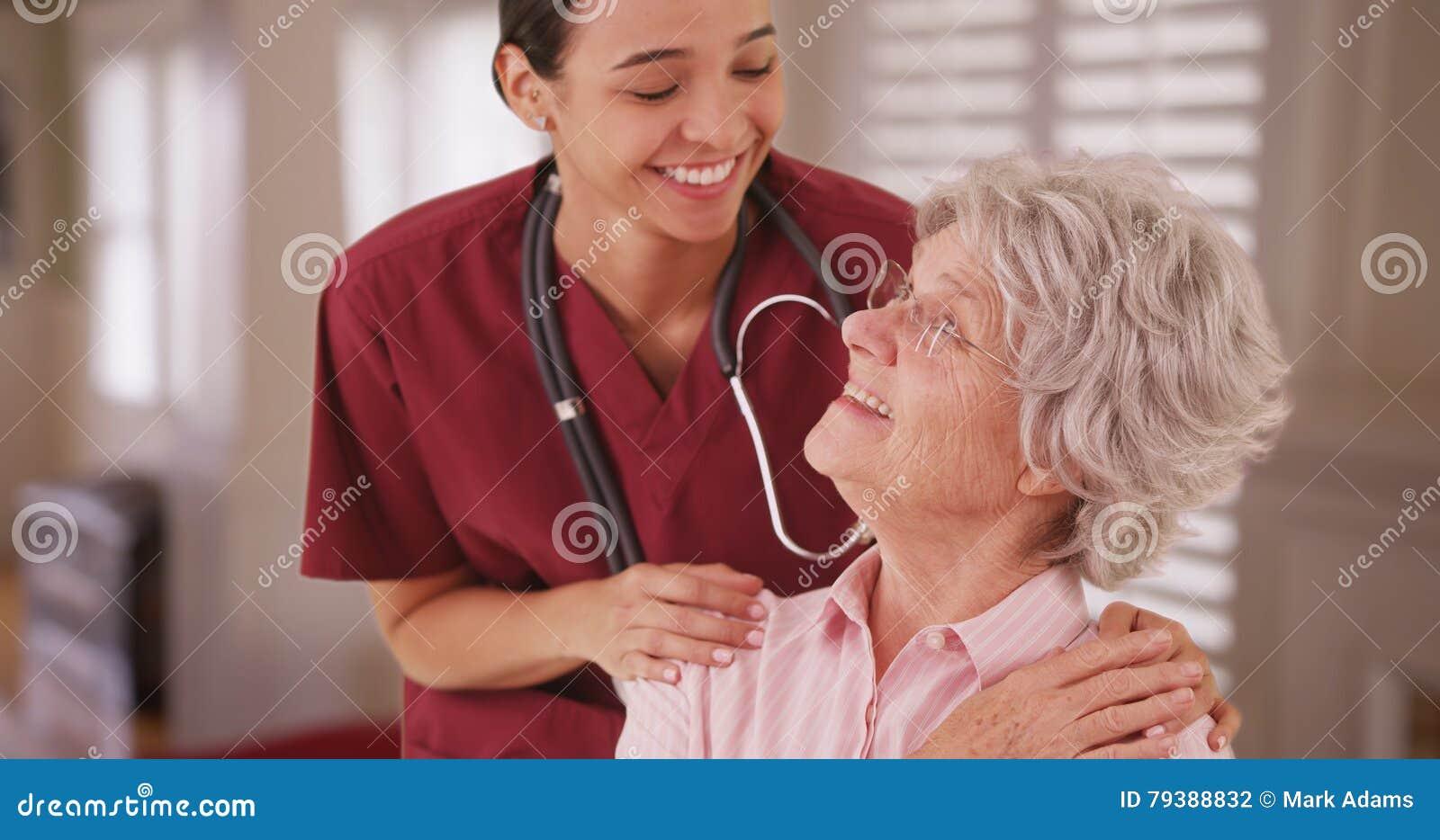 Hispanic female nurse looking and smiling with senior caucasian