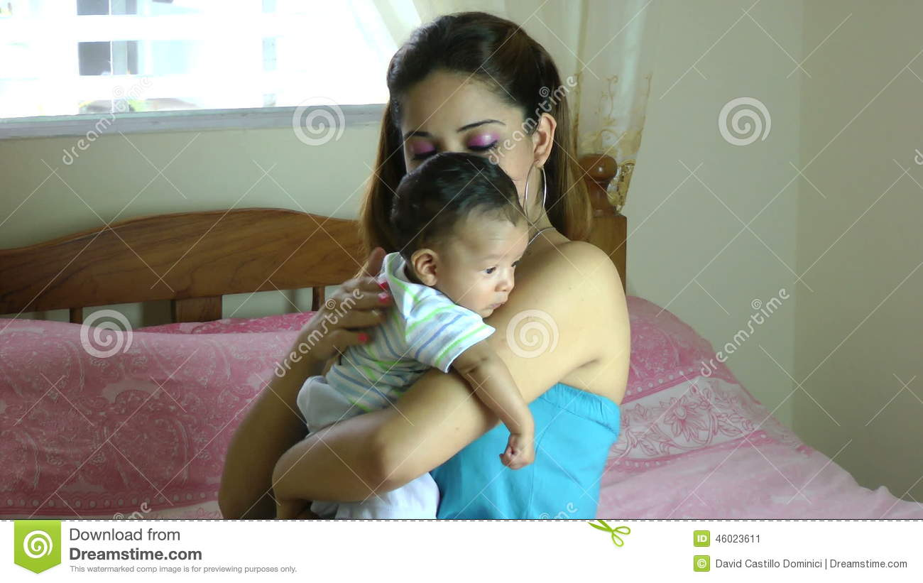 Hispanic Latina mother holding drooling baby over shoulder and tapping on  back so infant can burp
