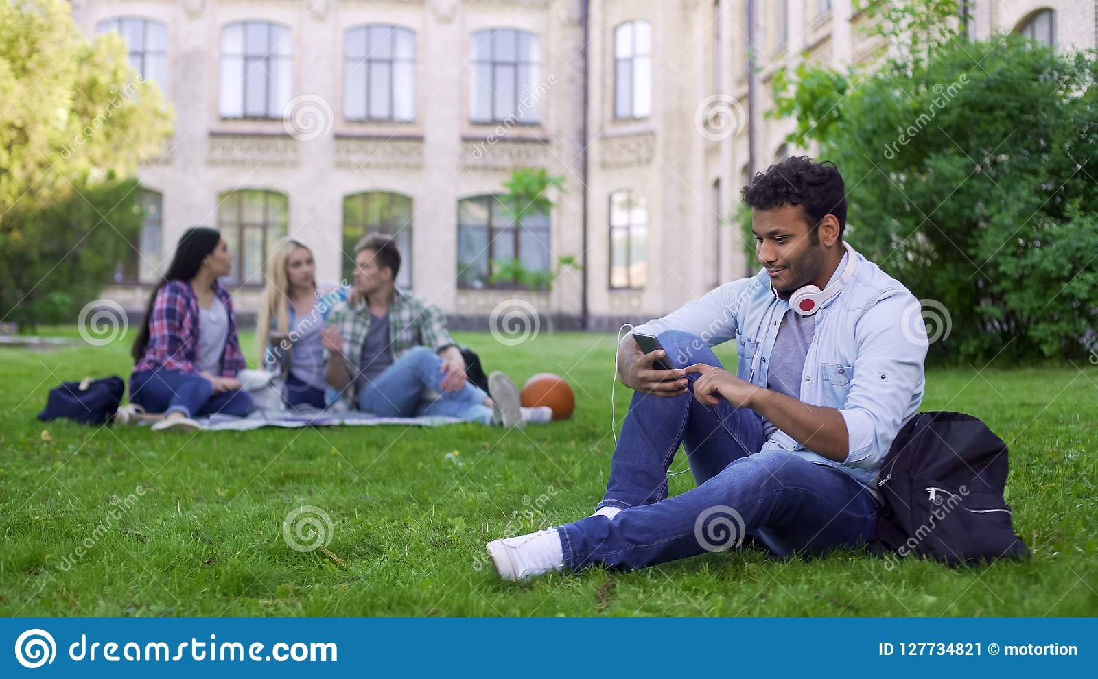 Hispanic male student sitting on grass and using cellphone, app for acquaintance